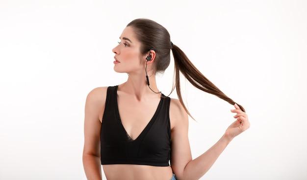 Brunette vrouw in joggen zwarte top luisteren naar muziek op oortelefoons poseren op grijs