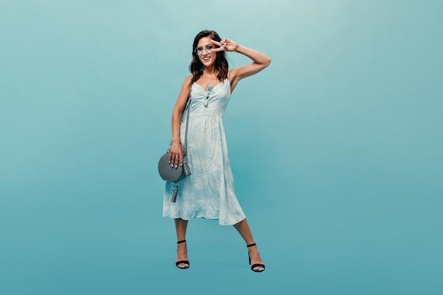 Brunette vrouw in jurk en stijlvolle bril toont vredesteken op blauwe achtergrond. leuke volwassen vrouw in modieuze outfit en in zwarte schoenen lacht.