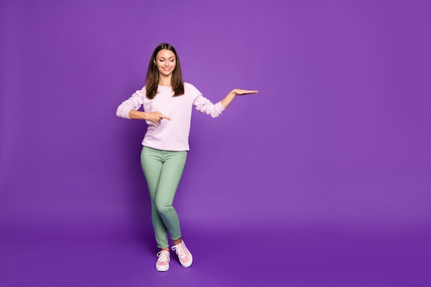 Brunette vrouw in pastel trui poseren tegen de paarse muur