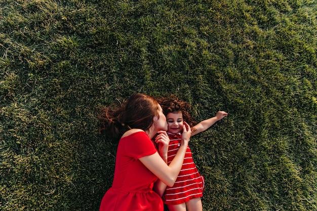Brunette vrouw in rode jurk liggend op het gras en kussen dochter in wang. buiten overhead portret van jonge moeder en haar kind chillen in park.