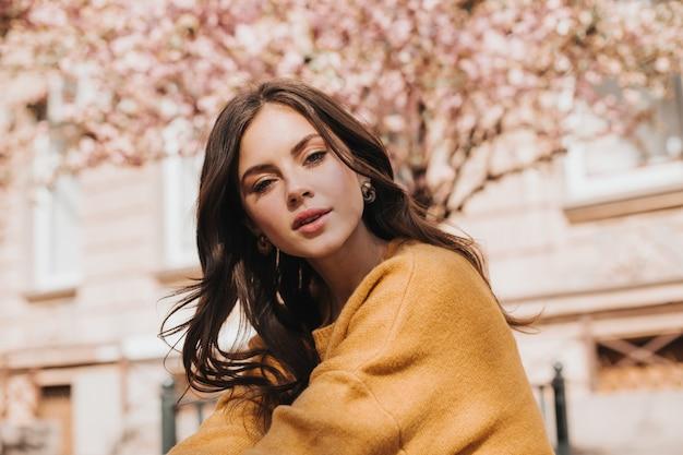 Brunette vrouw in stijlvolle trui kijkt naar de camera tegen de achtergrond van sakura. dame in gele outfit die gevoelig buiten poseert