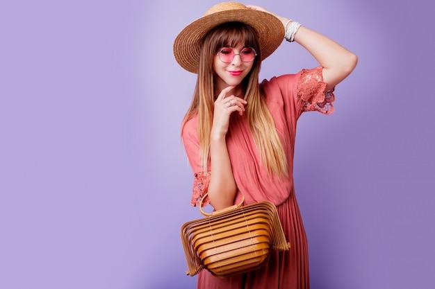 Brunette vrouw in trendy roze jurk en strooien hoed met bamboe tas op violet.