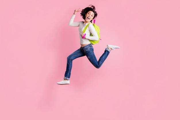 Brunette vrouw in witte trui springen met rugzak geïsoleerd op roze
