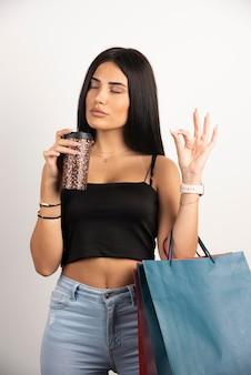 Brunette vrouw in zwarte top ruikende geur van koffie. hoge kwaliteit foto