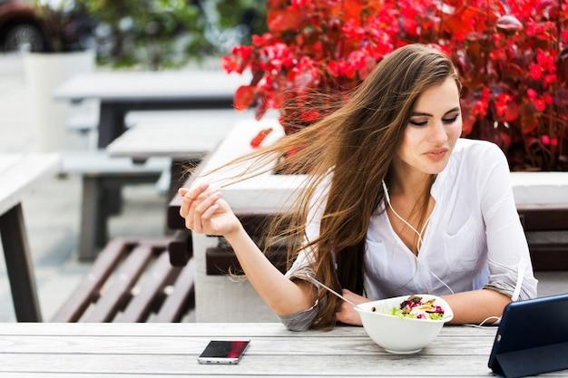 Brunette vrouw kijkt iets op haar tablet terwijl ze in het restaurant zit