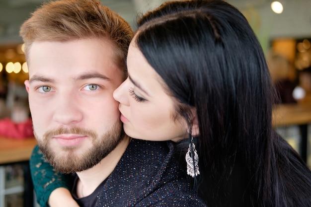 Brunette vrouw knuffelt haar blonde vriendje om zijn nek en kust hem