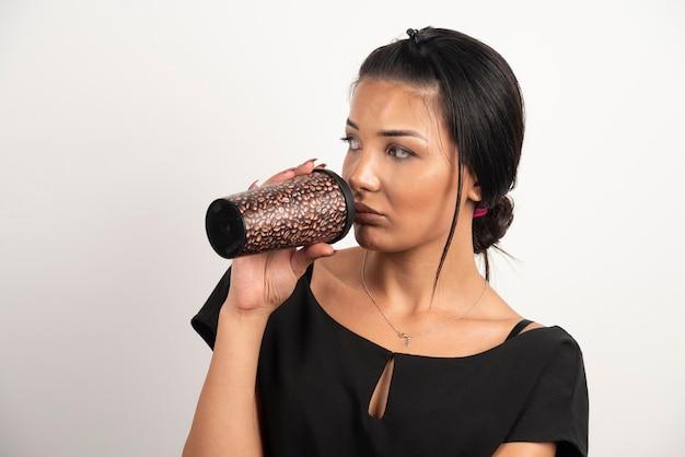 Brunette vrouw kopje koffie drinken op witte muur.