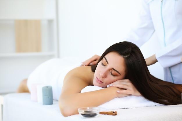 Brunette vrouw liggend met gesloten ogen op de voorkant van het lichaam terwijl