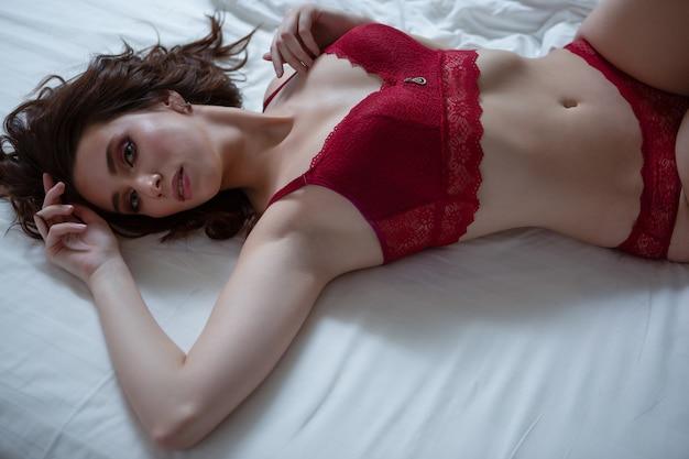 Brunette vrouw liggend op een bed in kanten ondergoed