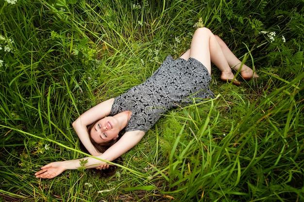 Brunette vrouw liggend op groen gras genieten van natuur en ontspanning