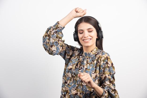 Brunette vrouw luisteren naar muziek en dansen met gelukkige uitdrukking.