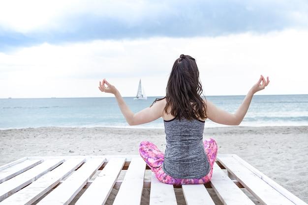 Brunette vrouw mediteert op een houten pier aan zee in de zomer tegen de achtergrond van de zee.