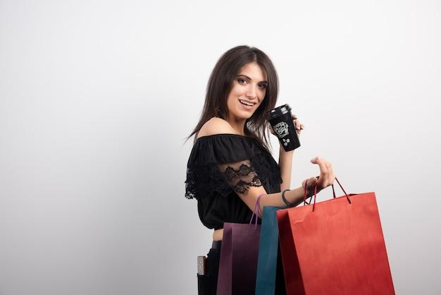 Brunette vrouw met boodschappentassen en koffiekopje.