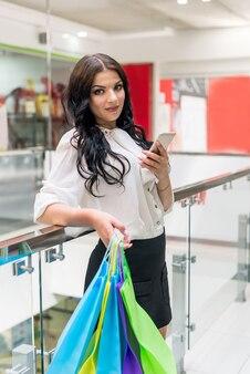 Brunette vrouw met boodschappentassen en smartphone