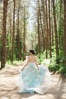 Brunette vrouw met een mooie jurk die in het bos loopt