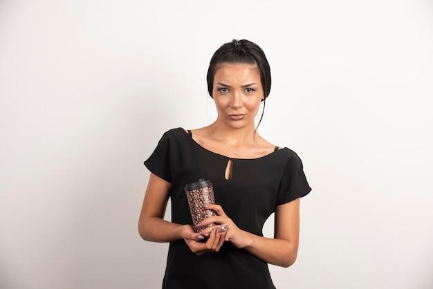 Brunette vrouw met kopje koffie poseren op witte muur.