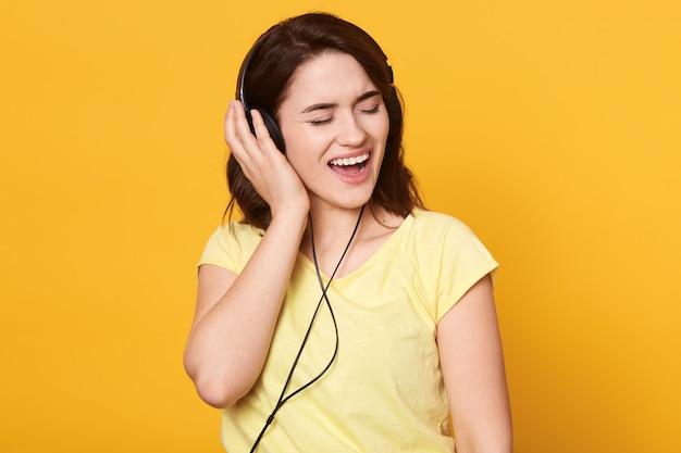 Brunette vrouw met koptelefoon luisteren naar favoriete muziek en zingen