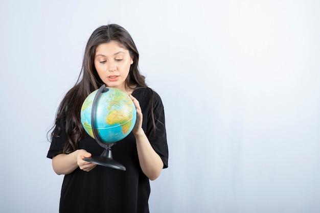 Brunette vrouw met lang haar kiest een plek om te reizen over de hele wereld