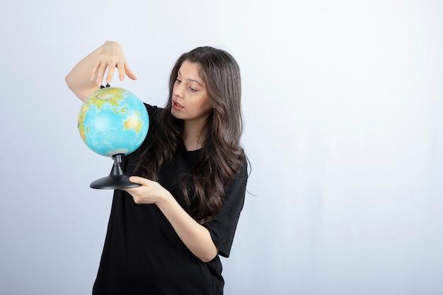 Brunette vrouw met lang haar kiest een plek om te reizen over de hele wereld.