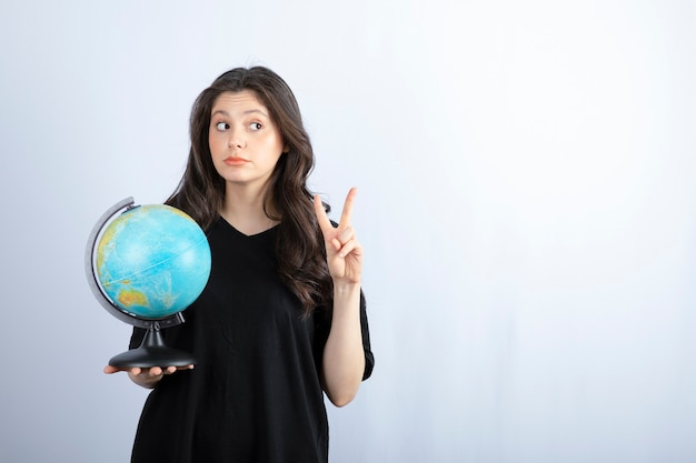Brunette vrouw met lang haar wereldbol te houden en poseren.
