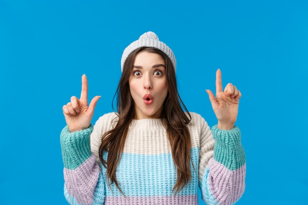 Brunette vrouw met winter hoed en trui wijst naar iets