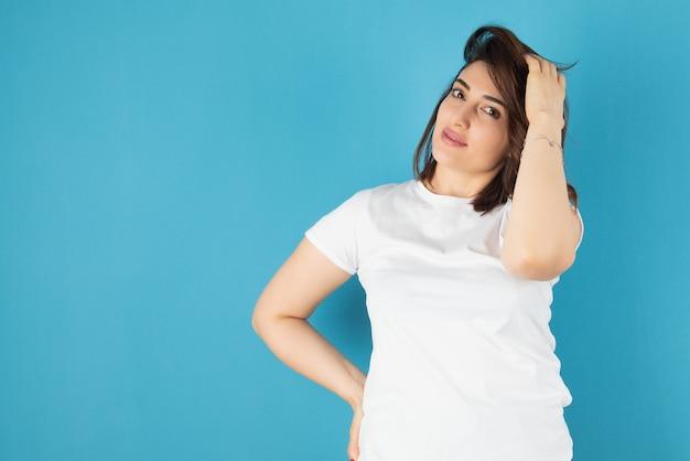 Brunette vrouw model permanent en poseren tegen blauwe muur