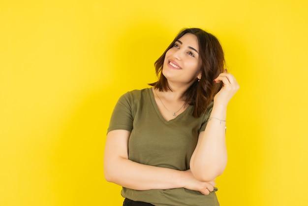 Brunette vrouw model permanent en poseren tegen gele muur