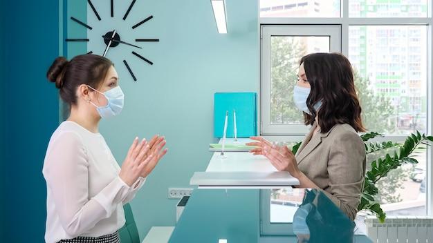 Brunette vrouw office manager met beschermend masker praat met dame patiënt staande bij de receptie tegen raam in ziekenhuis close zijaanzicht