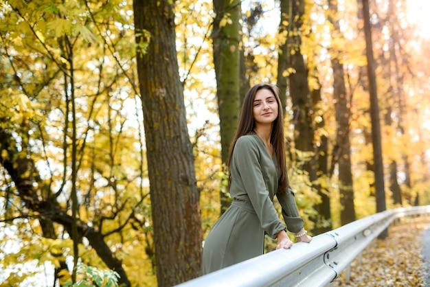 Brunette vrouw portret in herfst park olijf jurk dragen