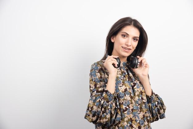 Brunette vrouw poseren met koptelefoon op witte achtergrond.