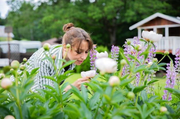 Brunette vrouw roze pioenroos bloemen snuiven temidden van lupine in rustieke stijltuin