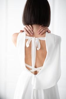Brunette vrouw stond voor een witte muur met haar rug naar de camera. witte jurk met mooie achterkant.