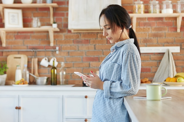 Brunette vrouw terloops gekleed, nagels heeft gelakt, kijkt serieus naar slimme telefoon