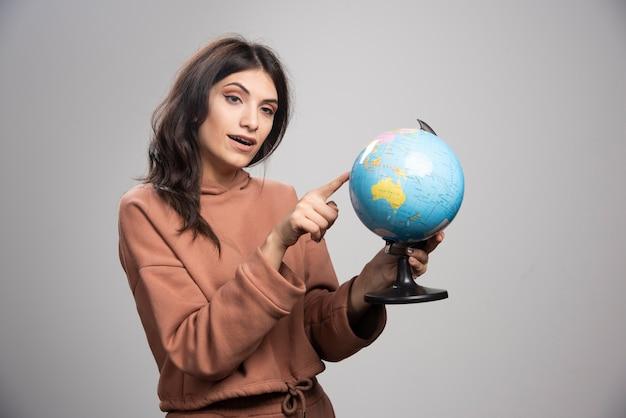 Brunette vrouw wijzend op kleine plaats op wereldbol