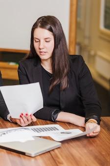 Brunette vrouw zit bij bureau lezen documenten