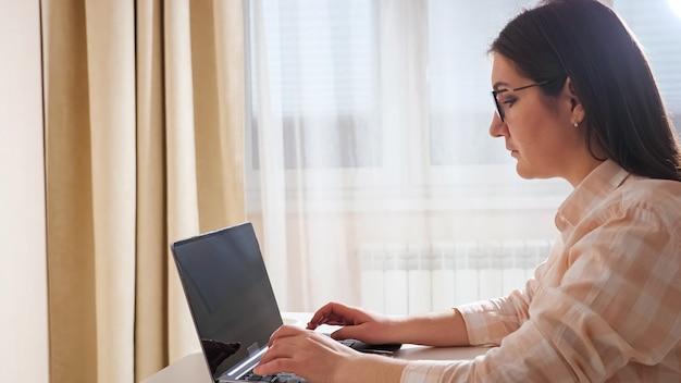 Brunette vrouw zittend aan de tafel, typen op de laptop op de achtergrond van het venster.
