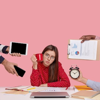 Brunette vrouw zittend aan een bureau omringd met gadgets en papieren