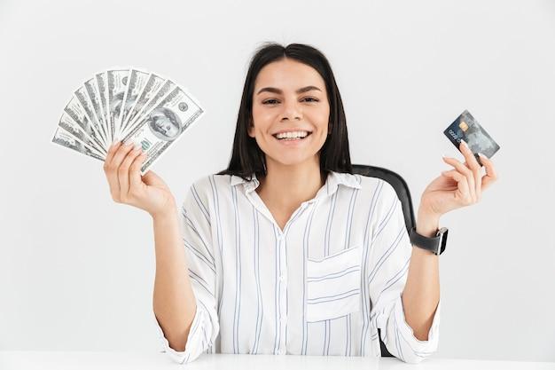 Brunette zakenvrouw bedrijf plastic creditcard en ventilator met dollar geld bankbiljetten zittend in fauteuil in kantoor geïsoleerd over witte muur