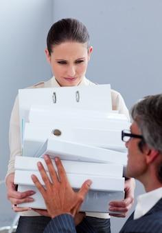 Brunette zakenvrouw en haar manager die een stapel mappen