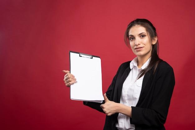 Brunette zakenvrouw klembord houden en duimen opgevend.