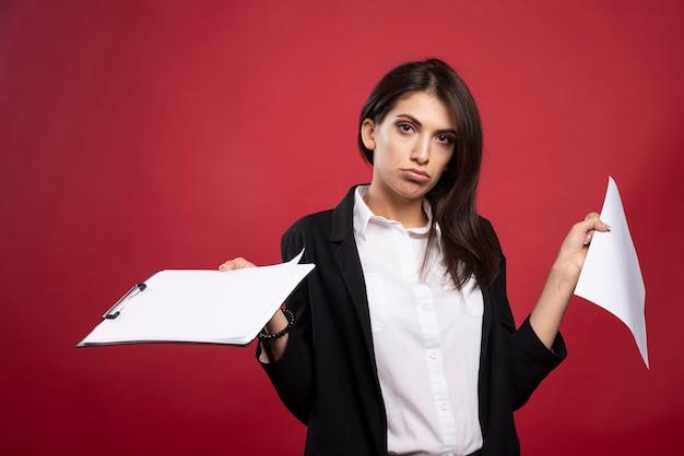 Brunette zakenvrouw met bos documenten op rode achtergrond.