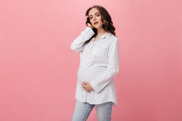 Brunette zwangere vrouw in wit overhemd onderzoekt camera. vrolijk jong meisje in spijkerbroek met zich meebrengt op geïsoleerde roze achtergrond.