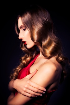 Brunetteluxury vrouw in rode jurk met heldere huid en donkere avond make-up: groen kattenoog en bruine oogschaduw. golvend kapsel. donkere achtergrond