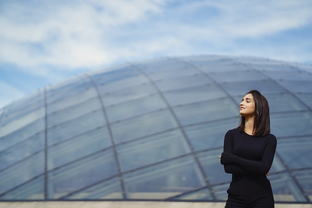 Brunetter meisje naast een modern gebouw