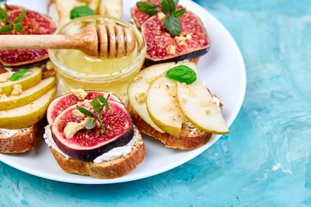 Bruschetta en crostini met peer, ricotta, honing, vijgen.