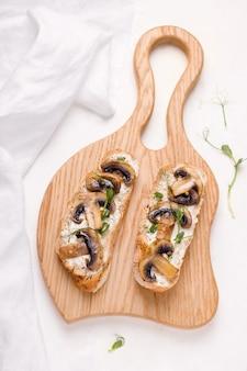 Bruschetta is een traditioneel italiaans voorgerecht. sandwich met champignons en micro greens op een witte achtergrond.