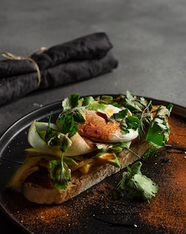 Bruschetta met cottage sheese en schijfje komkommer avocado gepocheerd ei
