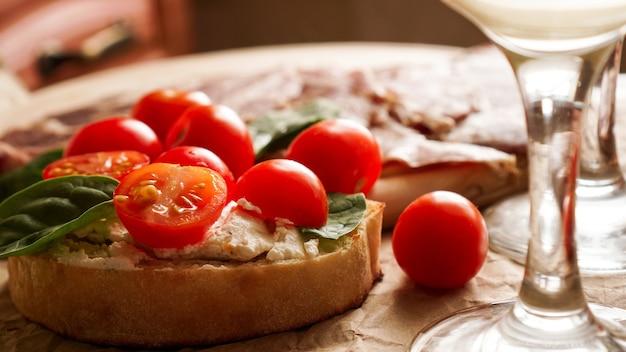 Bruschetta met kerstomaatjes. wijnglas, italiaans voorgerecht. ambachtelijke papier achtergrond. picknick concept