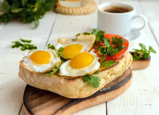 Bruschetta met kwarteleitje, paprika, kruiden en een kopje koffie. licht ontbijt.