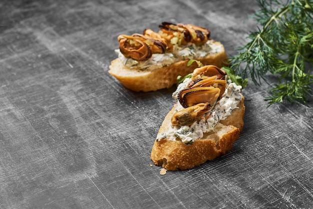 Bruschetta met mosselen en kaas plakken met rucola, sesam op houten achtergrond